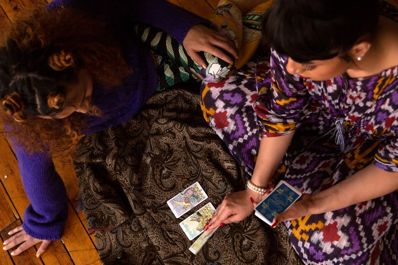 A genderfluid person and a transgender woman using practicing tarot.