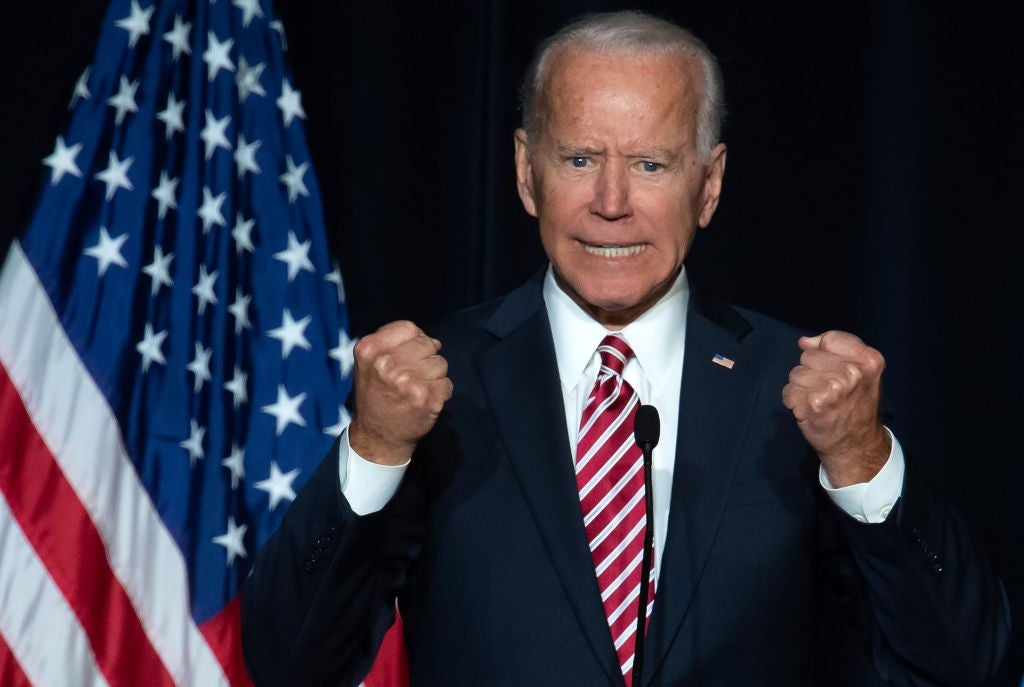 Biden clutches his fists dramatically while speaking against a dark blue backdrop and next to an American flag.