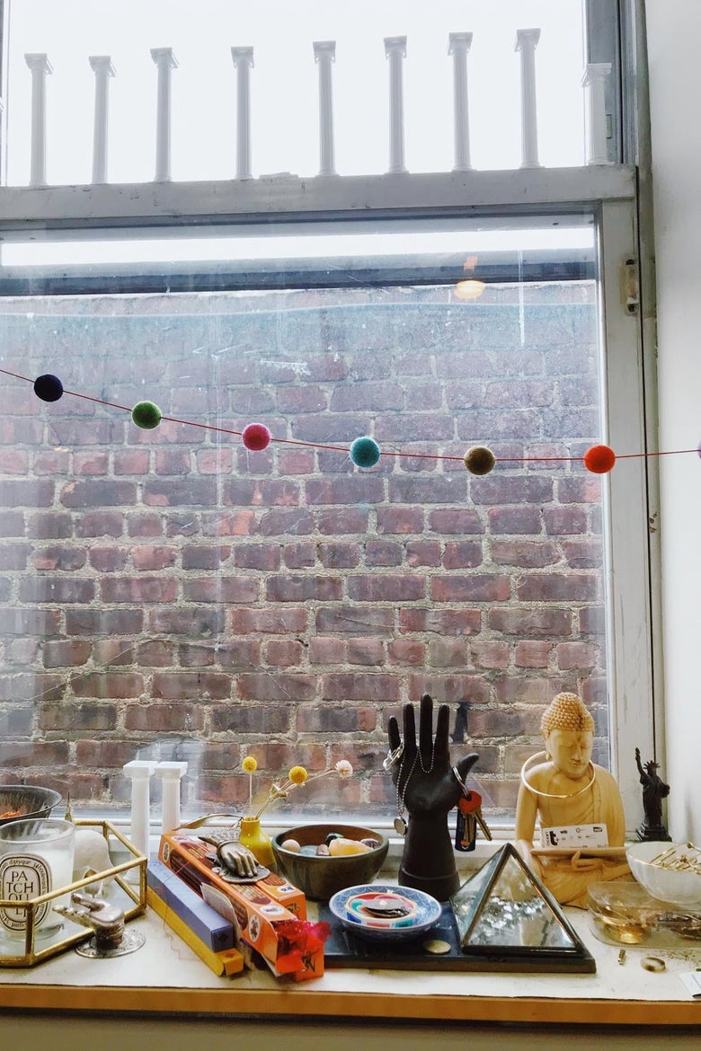 A window facing a brick wall with a windowsill filled with colorful things in the foreground.