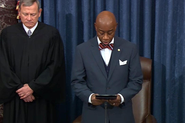 Roberts bows his head as Black reads from a book.