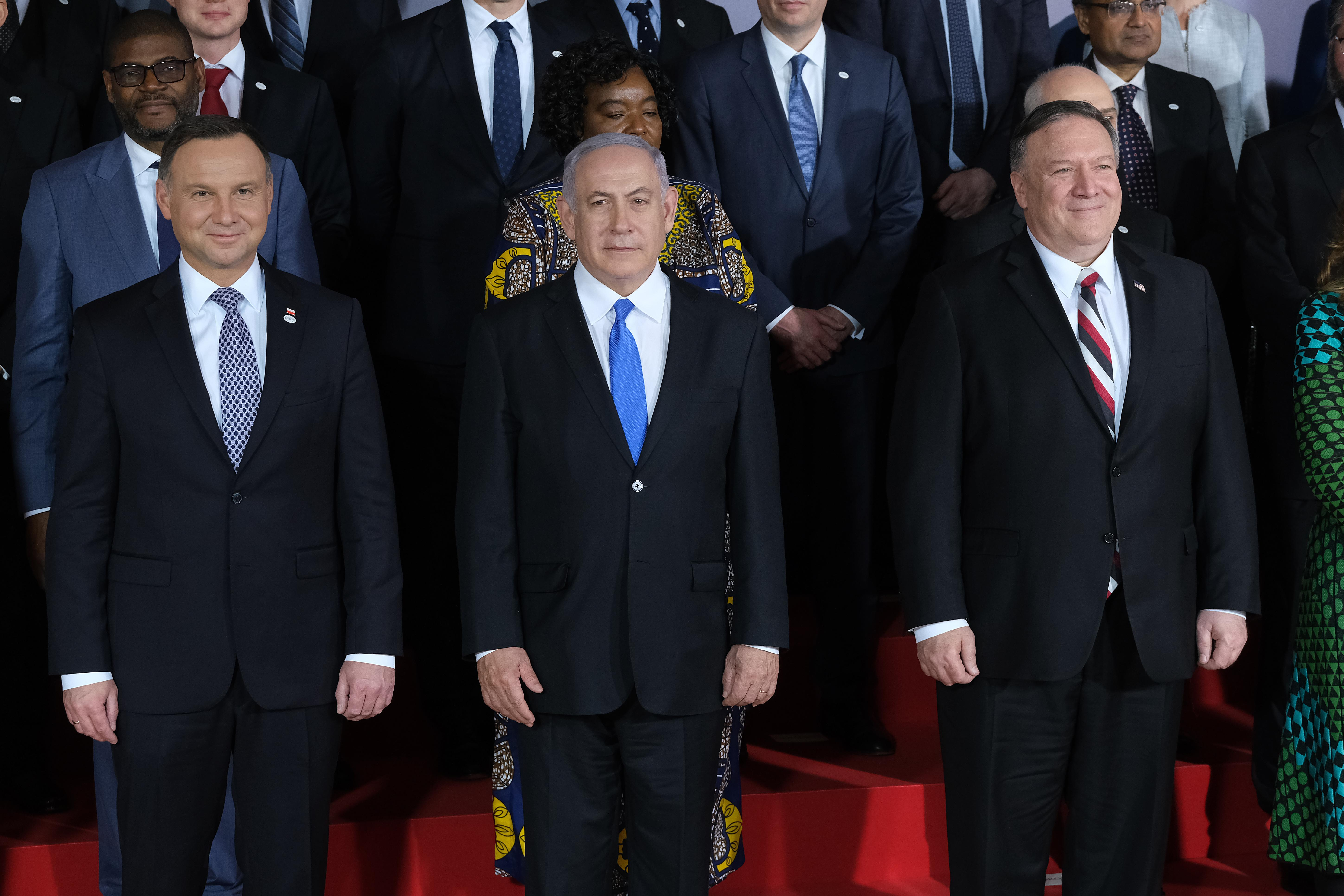 Andrzej Duda, Benjamin Netanyahu, and Mike Pompeo wearing suits and posing for a group photo.