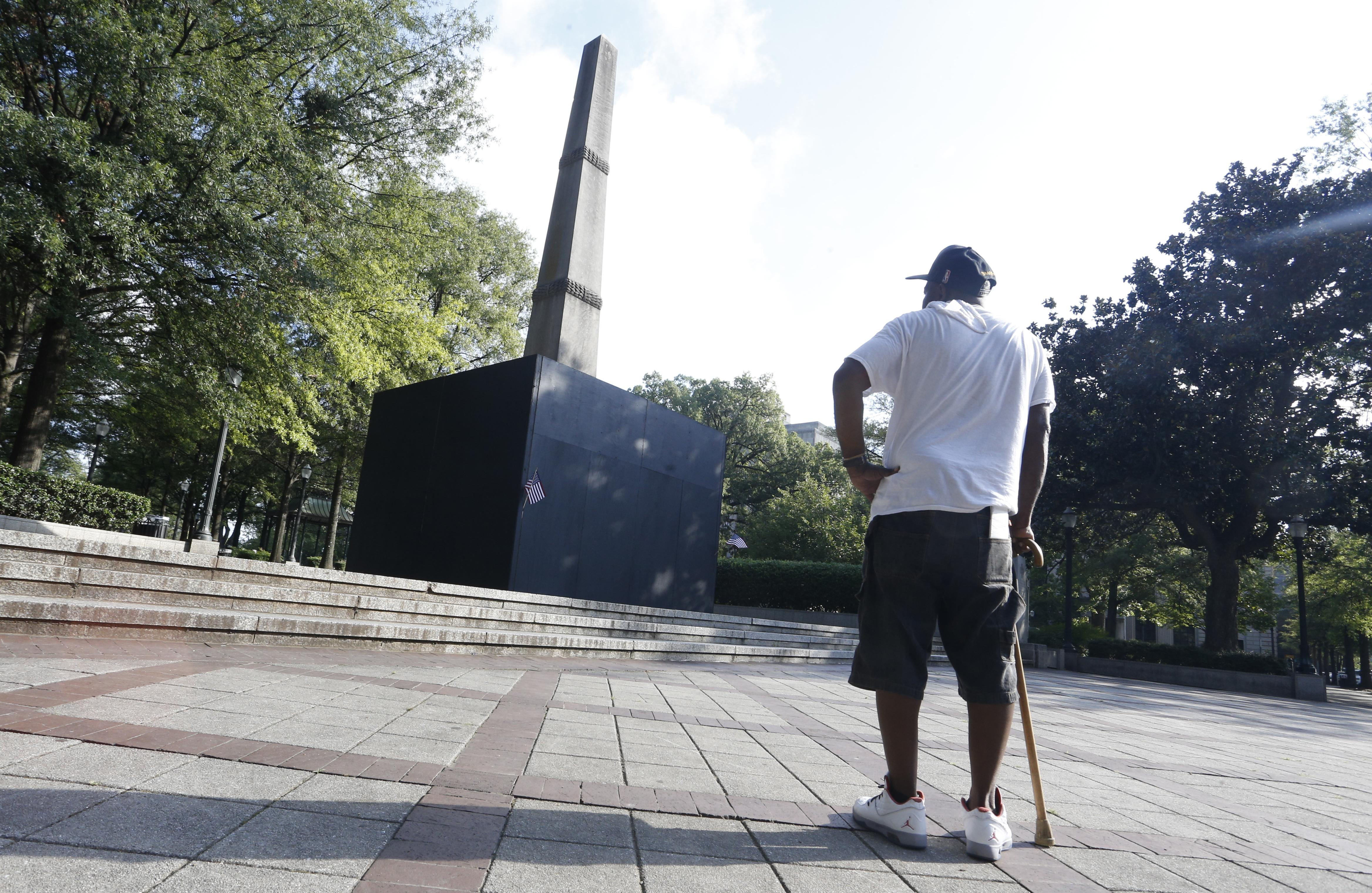 A man with a cane pauses to look at a now covered confederate monument in Linn Park in Birmingham, Alabama.