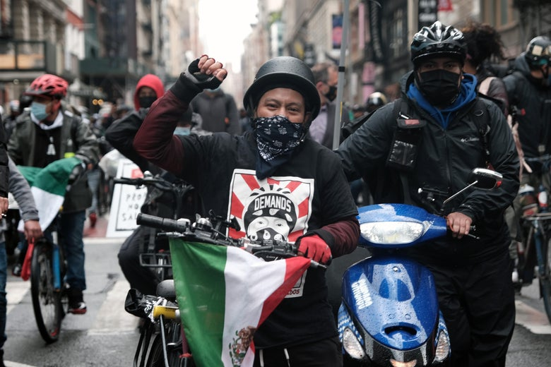 A man on a bike raises his fist in a march down a city street