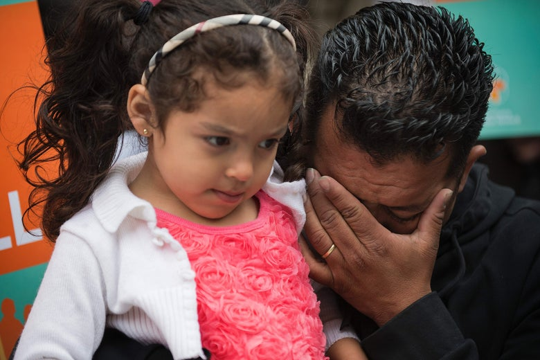 From right, Rene Bermudez wipes away tears as he holds his 4-year-old daughter Danyca during a protest on behalf of his wife Liliana Cruz Mendez on May 23.