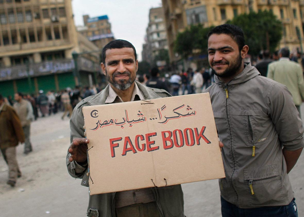 Anti-government protesters hold a sign referencing the Facebook social networking website that has been important in organizing protesters in Tahrir Square