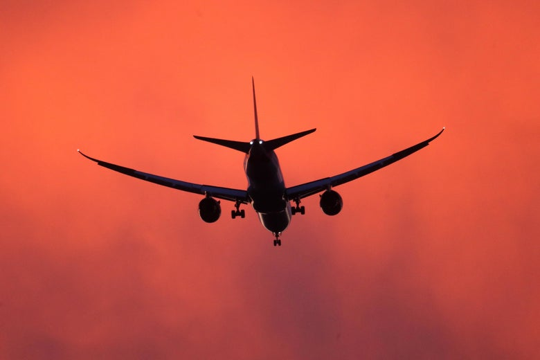 An airplane comes in to land at sunset.