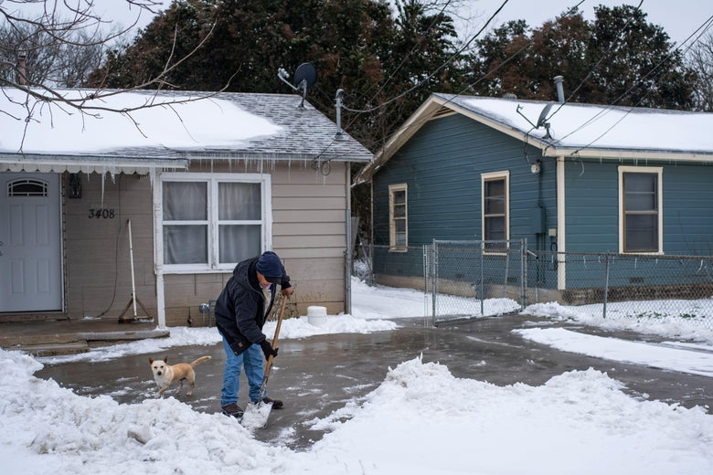 A man shovels snow from his driveway as his dog stands nearby.