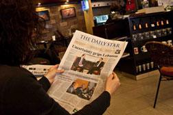 A woman reads Thursday's edition of Beirut's Daily Star at Café Younes in Hamra, Beirut. Click image to expand.