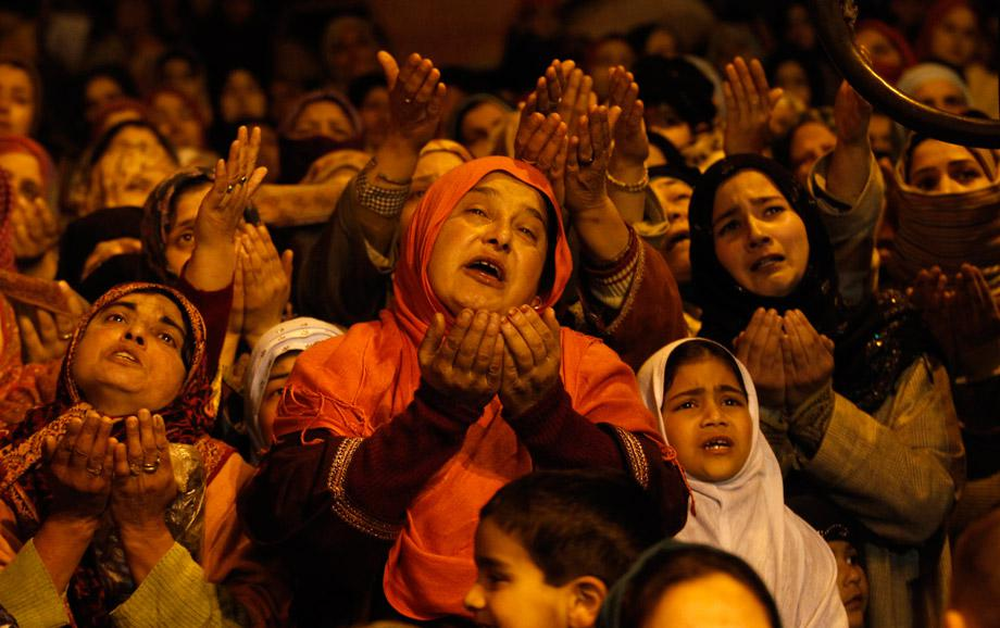Kashmiri Muslims raise their arms upon seeing a relic of Sheikh Abdul Qadir Jeelani, a Sufi saint, being displayed to devotees during the Friday following at his shrine in Srinagar March 1, 2013.