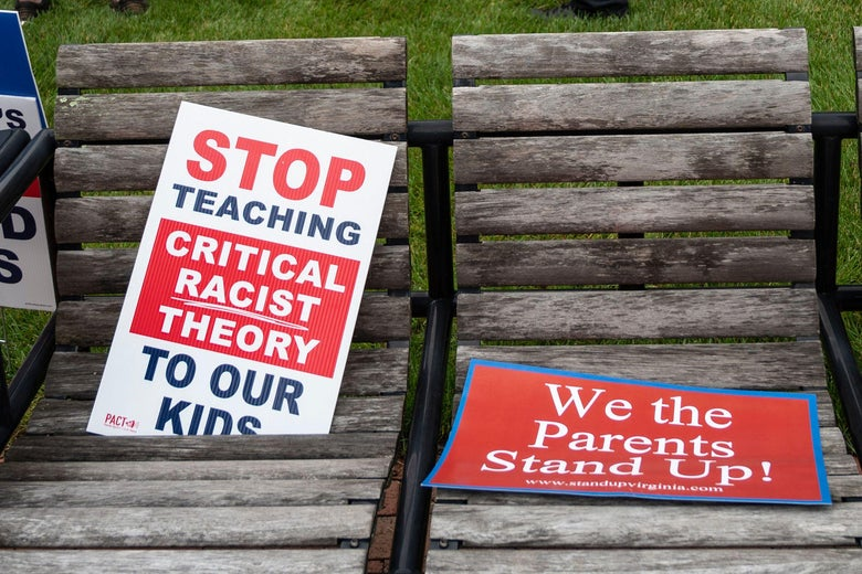 """Signs are seen on a bench during a rally against """"critical race theory"""" (CRT) being taught in schools at the Loudoun County Government center in Leesburg, Virginia on June 12, 2021. - """"Are you ready to take back our schools?"""" Republican activist Patti Menders shouted at a rally opposing anti-racism teaching that critics like her say trains white children to see themselves as """"oppressors."""" """"Yes!"""", answered in unison the hundreds of demonstrators gathered this weekend near Washington to fight against """"critical race theory,"""" the latest battleground of America's ongoing culture wars. The term """"critical race theory"""" defines a strand of thought that appeared in American law schools in the late 1970s and which looks at racism as a system, enabled by laws and institutions, rather than at the level of individual prejudices. But critics use it as a catch-all phrase that attacks teachers' efforts to confront dark episodes in American history, including slavery and segregation, as well as to tackle racist stereotypes. (Photo by ANDREW CABALLERO-REYNOLDS / AFP) (Photo by ANDREW CABALLERO-REYNOLDS/AFP via Getty Images)"""