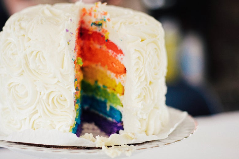 A rainbow cake that has had a slice cut out of it, revealing the colorful layers