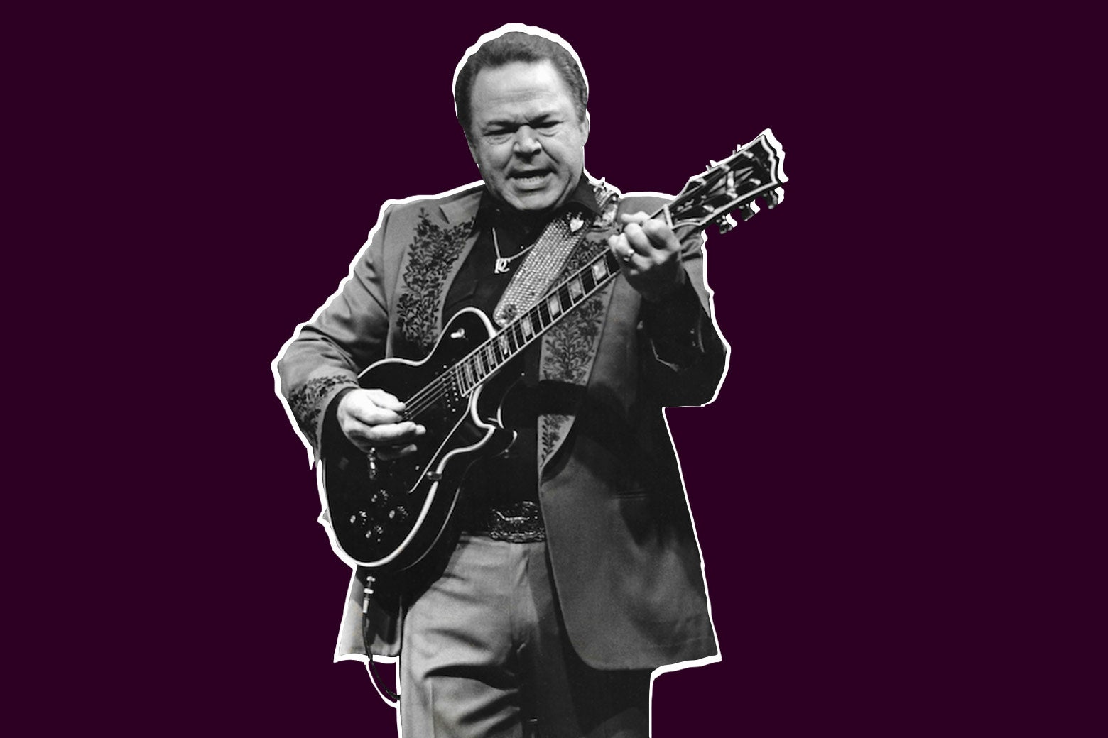 A young Roy Clark strums a guitar.
