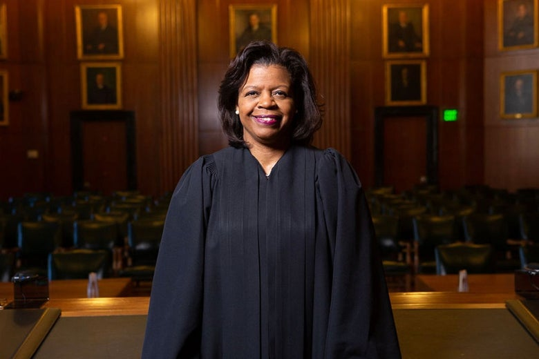 Cheri Beasley smiling in her robes, standing in a courtroom.