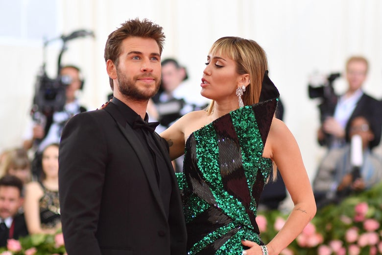 Miley Cyrus (R) and Liam Hemsworth stand on the red carpet at the 2019 Met Gala.
