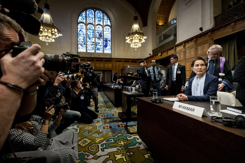 """Aung San Suu Kyi sits behind a placard marked """"Myanmar"""" in a courtroom. Photographers to her left hold up cameras to take pictures of her."""