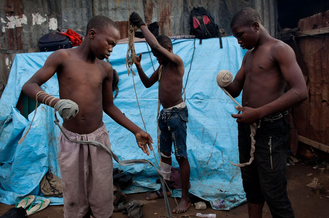 "Lagos, Nigeria- Young boxers prepare for their match by tightly wrapping the ""spear"", or striking arm, with material or rope. If the rope becomes undone during the match, the fight is stopped and the ""spear"" must be rewrapped before continuing."