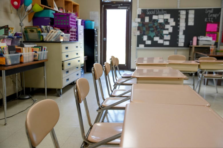 Empty chairs and desks are seen in a classroom.