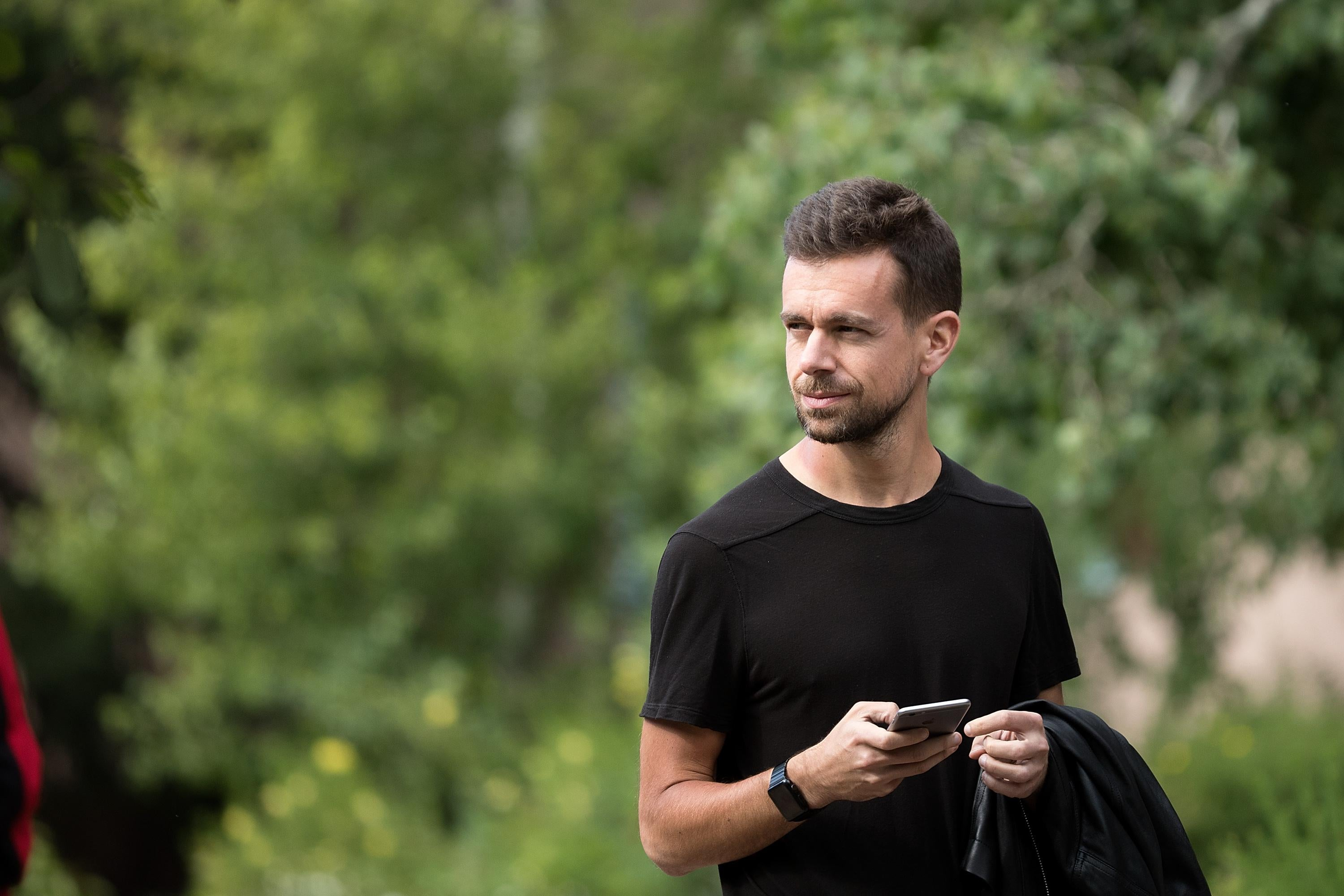 Jack Dorsey in front of some greenery, wearing all black, and holding his mobile phone.