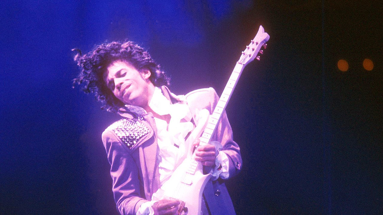 Prince, bathed in purple light, holds a guitar.