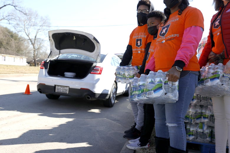 Volunteers prepare to load cases of water into cars during a water distribution at the Astros Youth Academy on February 20, 2021 in Houston, Texas.