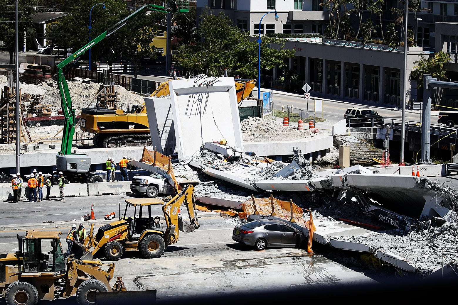 Law enforcement and members of the National Transportation Safety Board investigate the scene where a pedestrian bridge collapsed a few days in Miami, Florida.