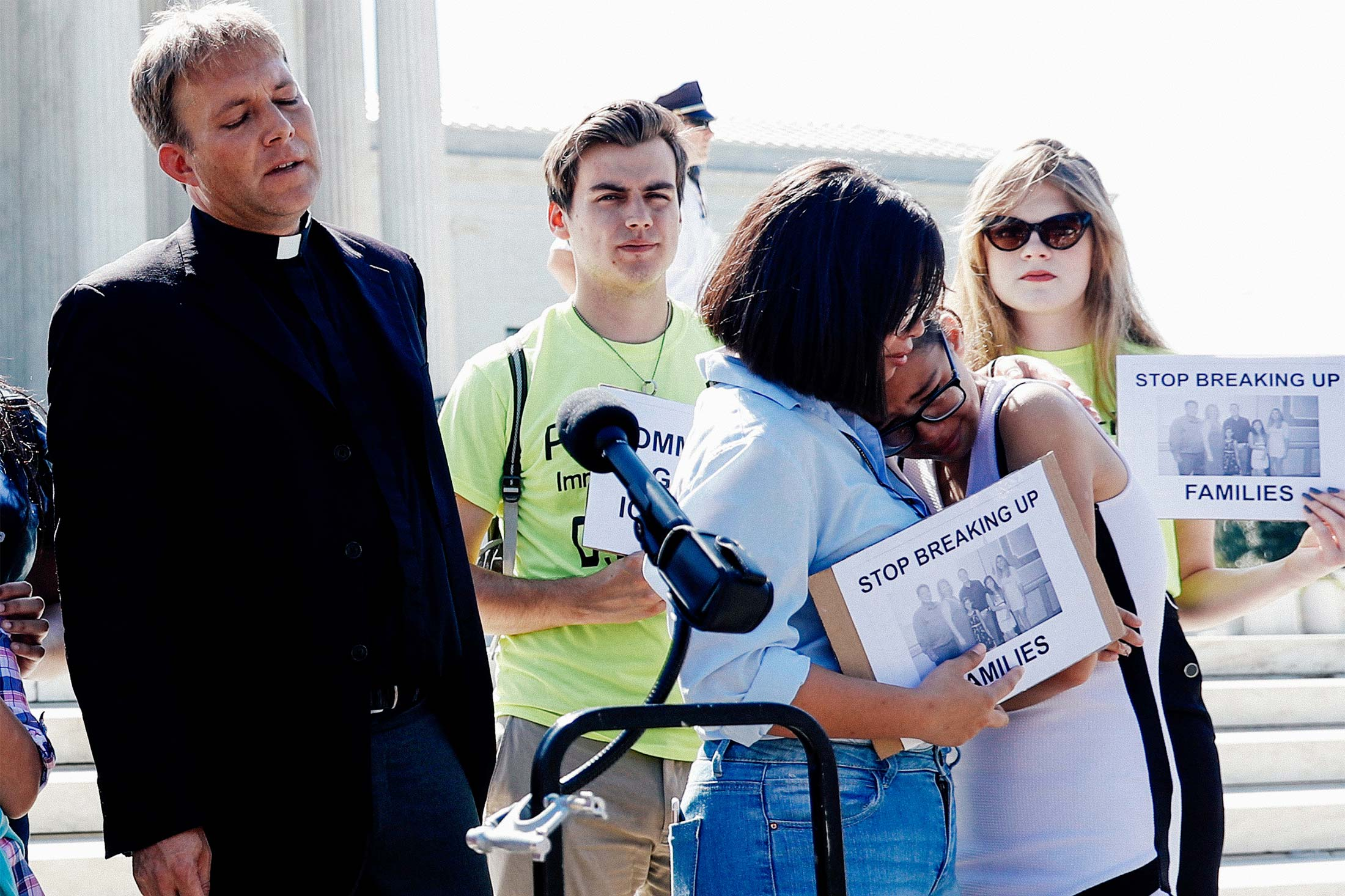 The Rev. Seth Kaper-Dale looks on as sisters Michelle Edralin, 12, and Nicole Edralin, 15, react with immigration rights proponents outside the U.S. Supreme Court after it upheld President Donald Trump's travel ban on Tuesday.
