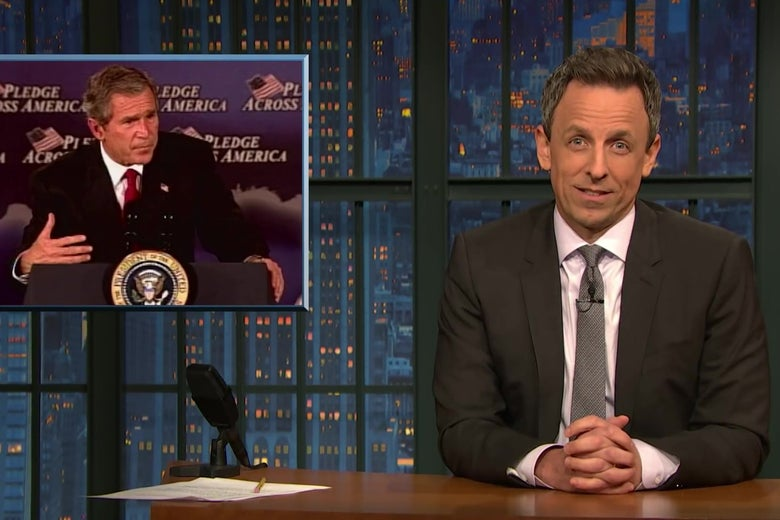 Seth Meyers sits at an anchorperson's desk in front of a photo of George W. Bush giving a speech.