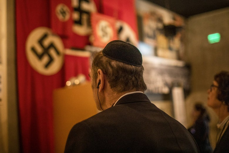 Man in a yamaka hat looks at a Nazi exhibit in Yad Vashem.