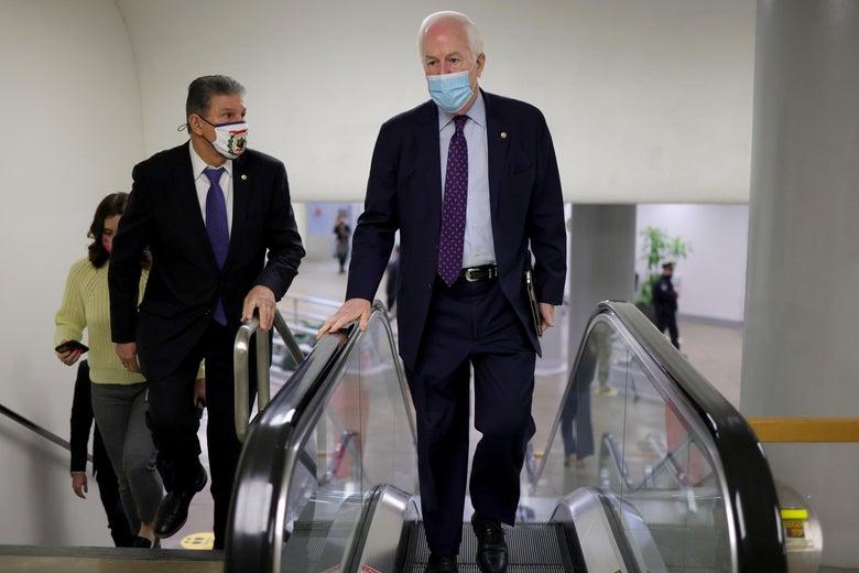 John Cornyn walks up an escalator as Joe Manchin walks up the stairs to the U.S. Senate chamber for a vote on March 5