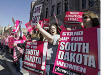 Demonstrators hold up signs as they protest South Dakota's new anti-abortion law outside the Federal Court building in Sioux Falls, S.D., Thursday, March 9, 2006. (AP Photo/Nati Harnik)