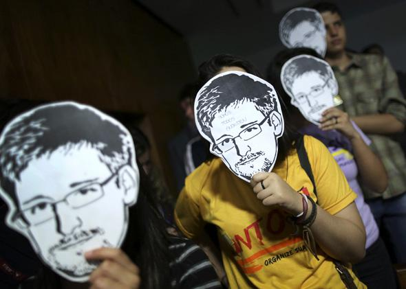 People use masks with pictures of former NSA contractor Edward Snowden masks during the testimonial of Glenn Greenwald.