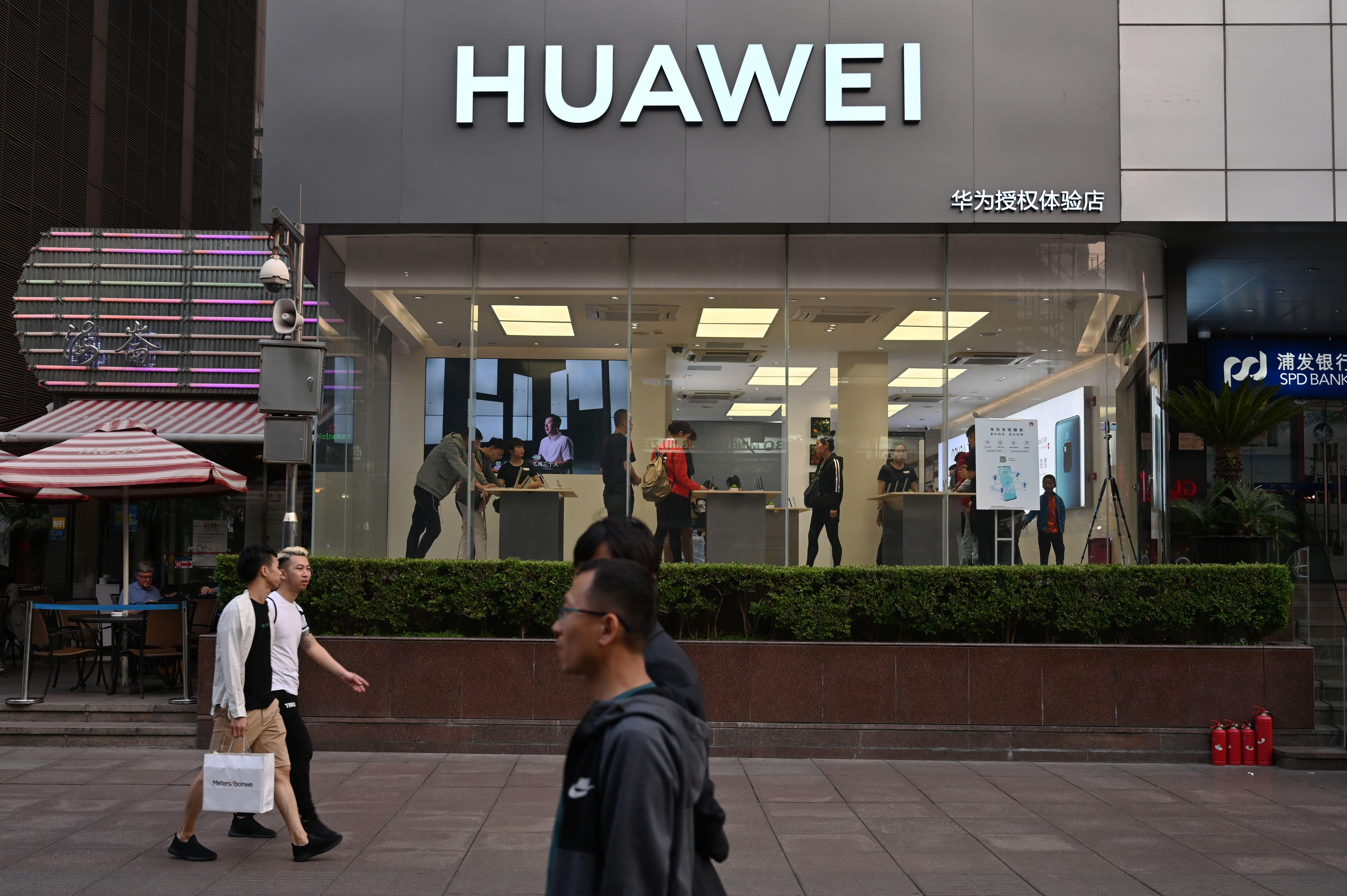 People walk past a Huawei store in Shanghai on May 10, 2019. (Photo by HECTOR RETAMAL / AFP)        (Photo credit should read HECTOR RETAMAL/AFP/Getty Images)