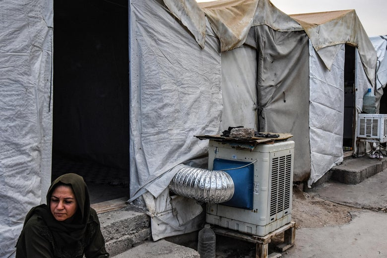 A woman sits outside a tent with an air-conditioning unit.