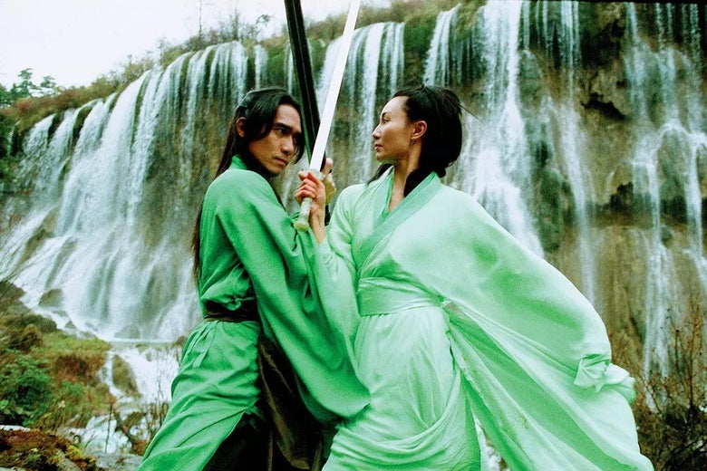In front of a waterfall, a man and woman, both wearing green, cross swords.