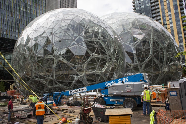SEATTLE, WA - JUNE 16: Workers surround the signature glass spheres under construction at the Amazon corporate headquarters on June 16, 2017 in Seattle, Washington. Amazon announced that it will buy Whole Foods Market, Inc. for over $13 billion dollars.  (Photo by David Ryder/Getty Images)