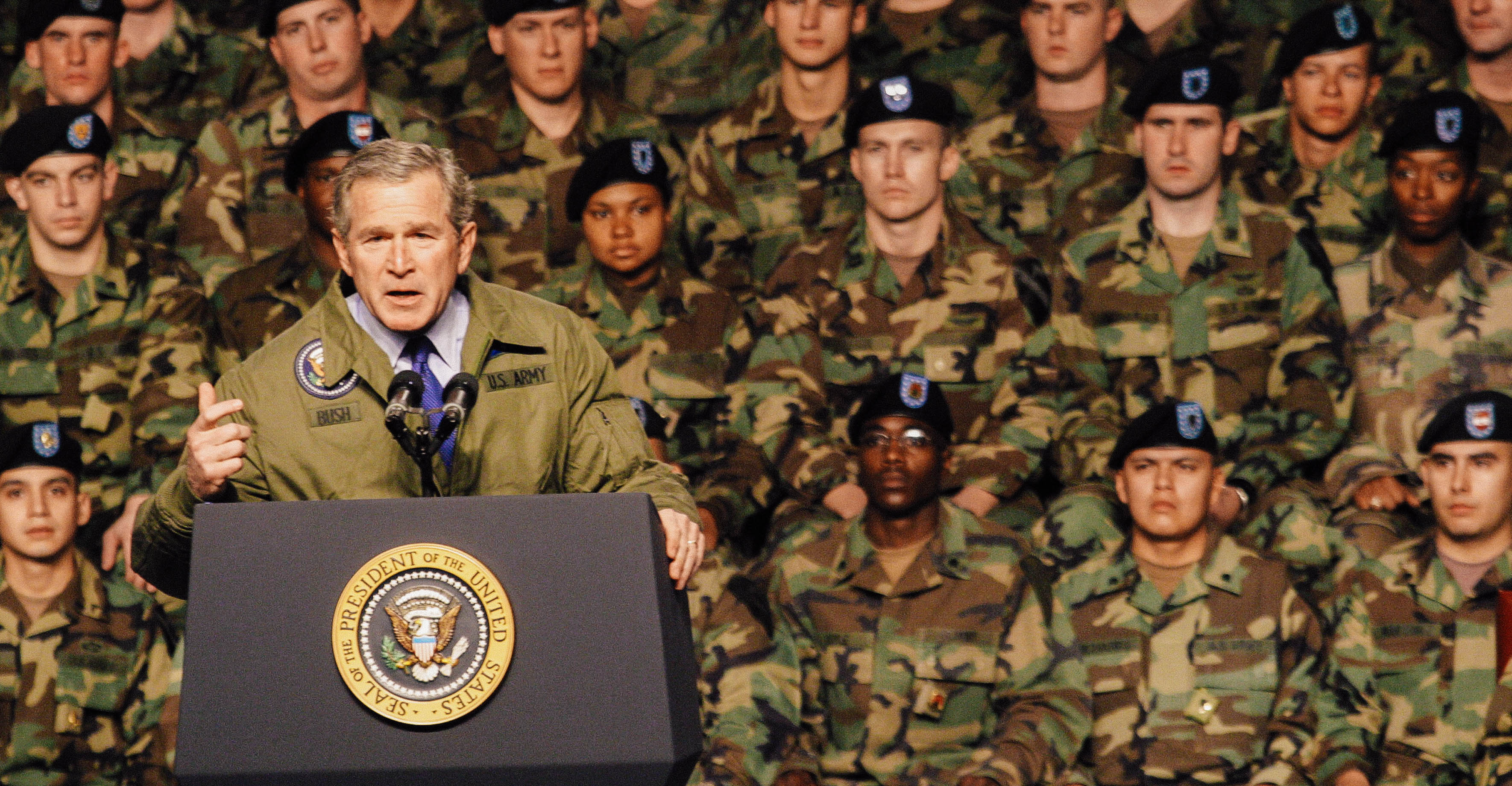 George W. Bush at a podium in front of U.S. troops in camouflage.