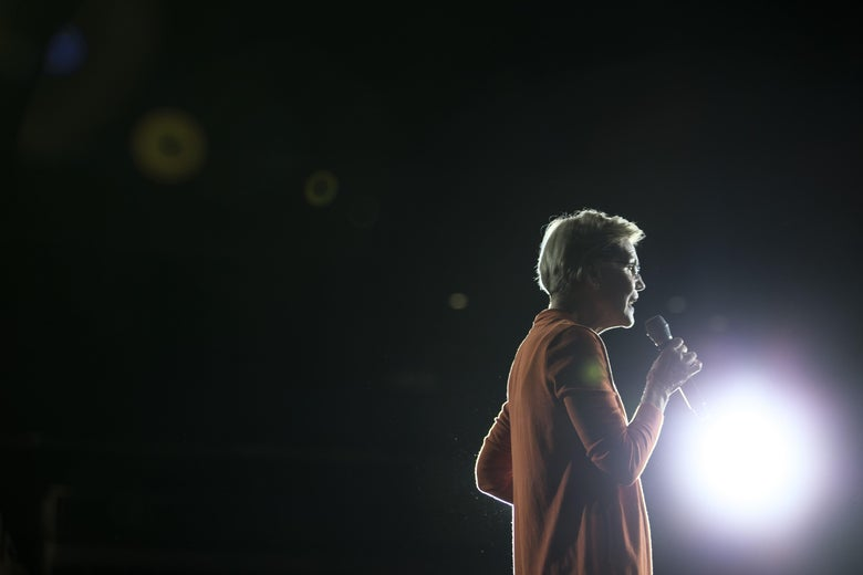 Elizabeth Warren speaks into a mic in front of a bright light onstage at a town hall event on Oct. 18 in Norfolk, Virginia.