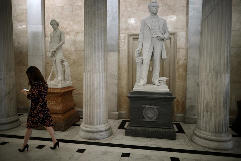 A woman walks past two statues, one of John E. Kenna