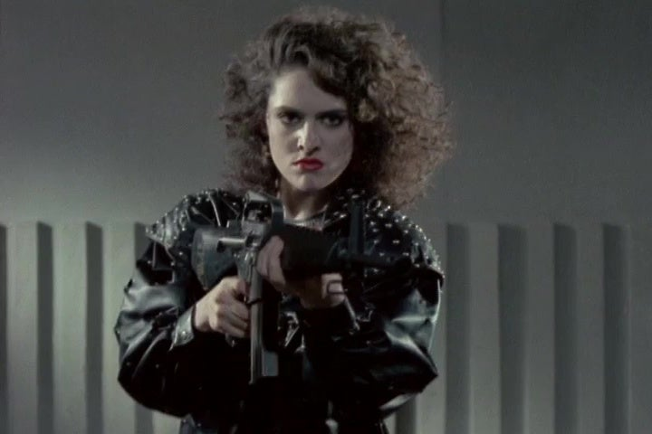 Barbara Anne Constable aims a machine gun at the screen in a still from Lady Terminator.
