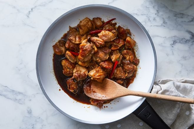 Chicken in a brown sauce with red peppers being mixed by a wooden spoon.