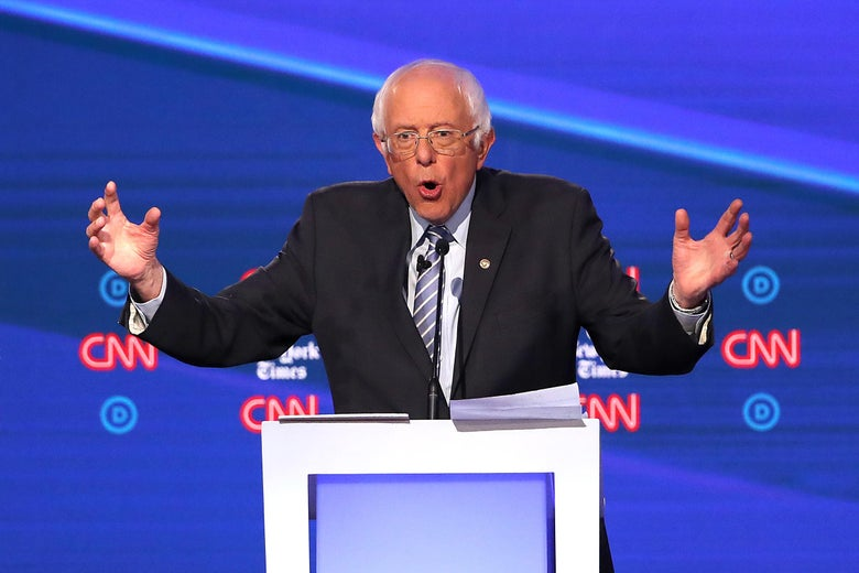 Bernie Sanders, midsentence, holds his arms out on the debate stage