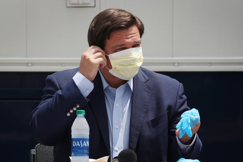 DeSantis wears a mask while speaking at a press conference.