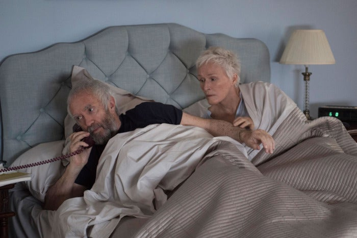 A man and woman lay in bed together while the man talks on the phone.