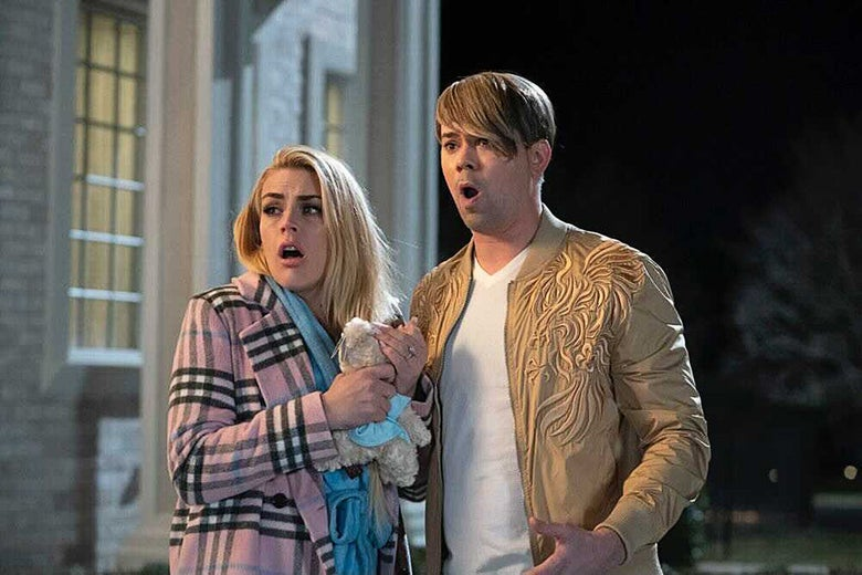 A woman in a pink plaid coat and a man with bleached-blond bangs.