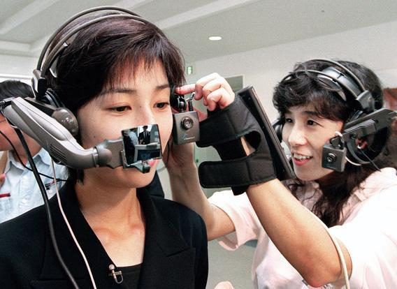 A woman helps another put American computer venture company Xybernaut's wearable PC 'Mobile Assistant IV' on her head.