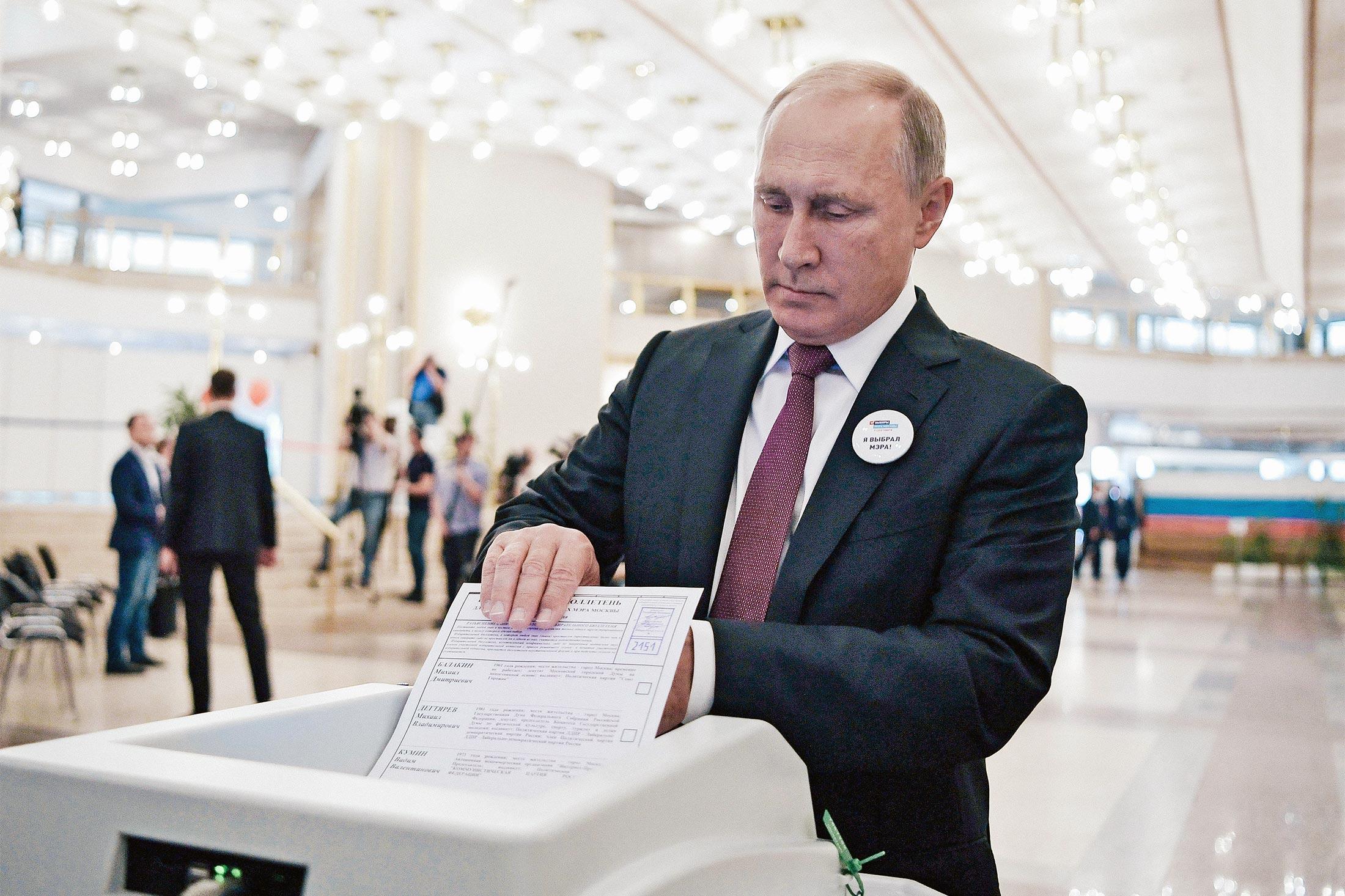 Vladimir Putin puts a ballot into an electronic reader.