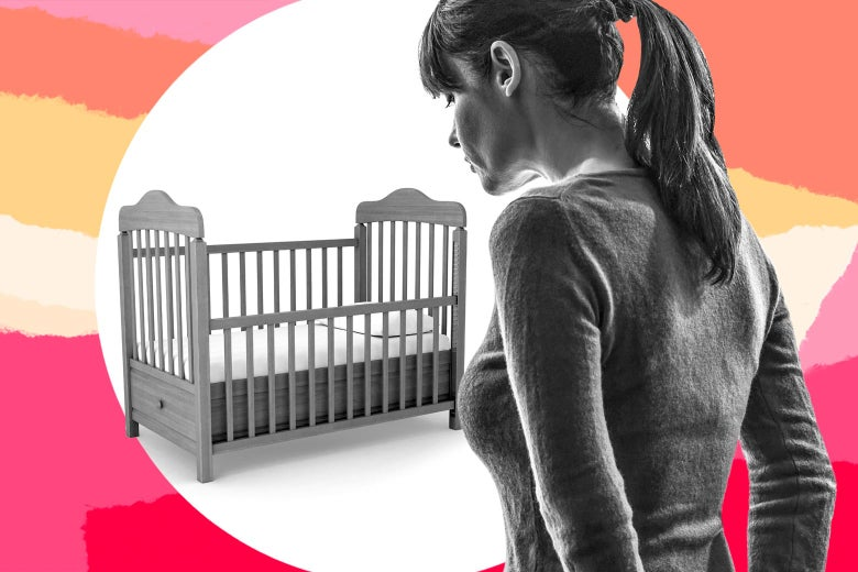 Woman looking into an empty crib.