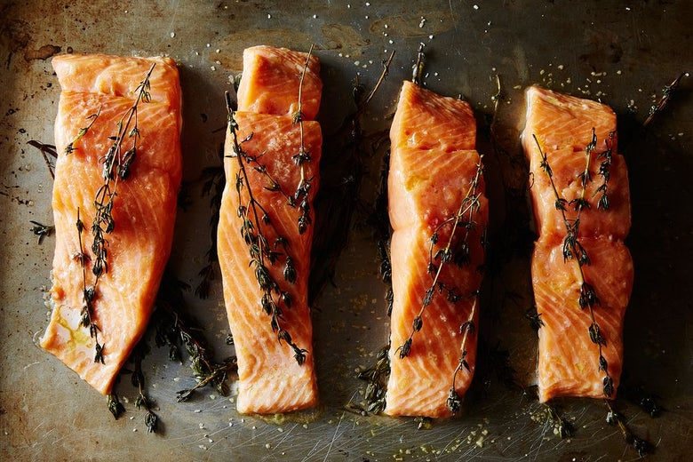 Raw salmon on baking sheet covered in herbs.