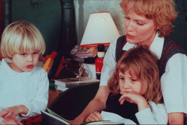 All three have long hair—Ronan's blonde hair is in a long bowl cut—as Mia appears to read to them from a children's book