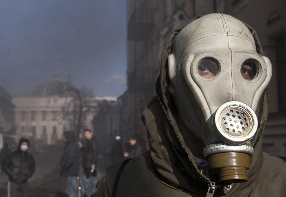 A protester wears a gas mask during clashes with Interior Ministry members in Kiev on Feb. 18, 2014. UKRAINE/